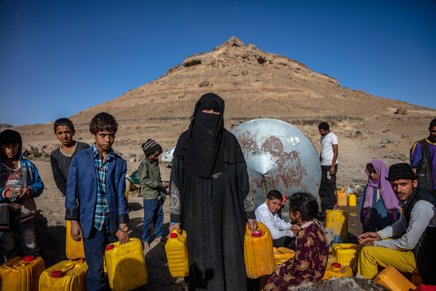 Image of women and children in arid outdoor environment in Yemen holding water canisters.
